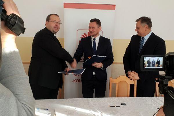 Wicemarszałek województwa Tomasz Sobieraj (w środku) i dyrektor Caritasu Diecezji Koszalińsko-Kołobrzeskiej ks.Tomasz Roda (z lewej) pogratulowali sobie parafowania obu umów. uwzględniającyh unijne dofinansowanie na rewitalizację