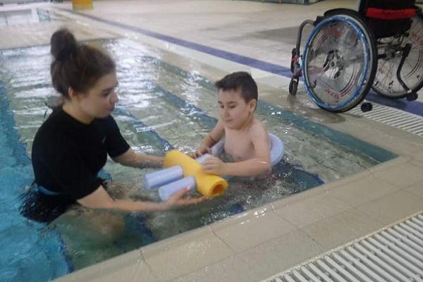 Zdjęcie przedstawia Adriana wraz z instruktorem pływania na basenie w wodzie.