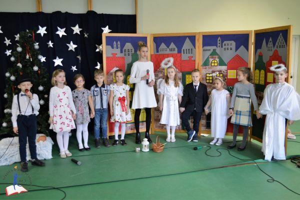 Zdjęcie przedstawia grupę dzieci - aktorów stojących na tle dekoracji - kamieniczek oraz gwieździstego nieba